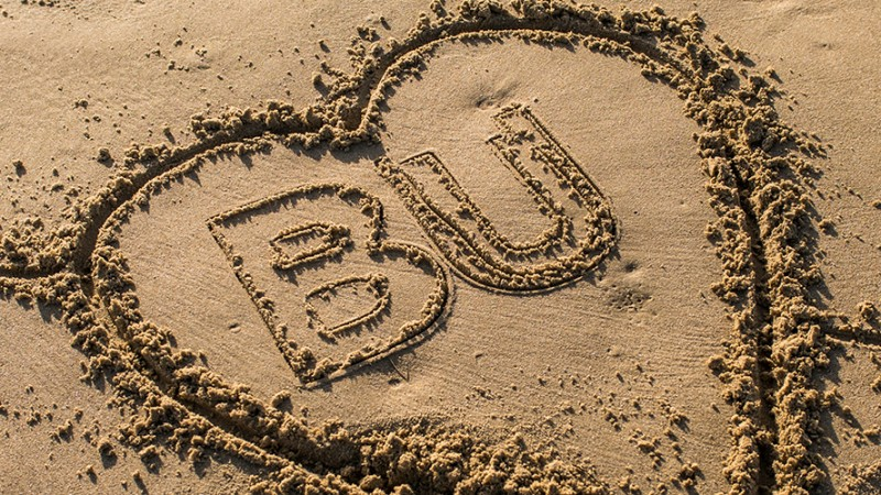 BU logo in a heart carved into beach