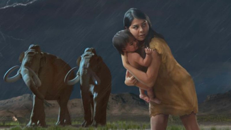A woman carrying a child with mammoths and wolves in the background