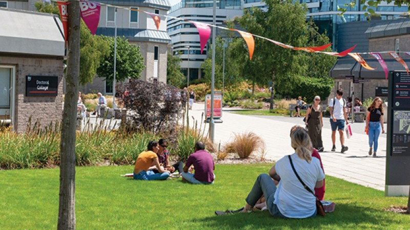 People sitting on grass outside Christchurch House on Talbot Campus on a sunny Open Day