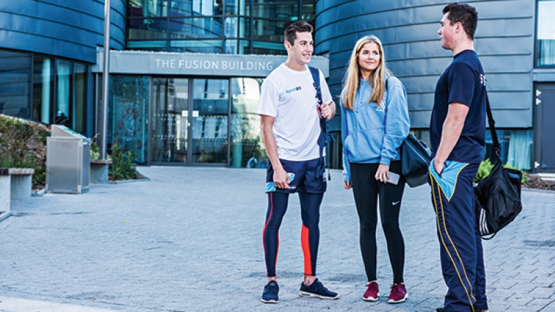 Students outside the Fusion Building in SportBU gear