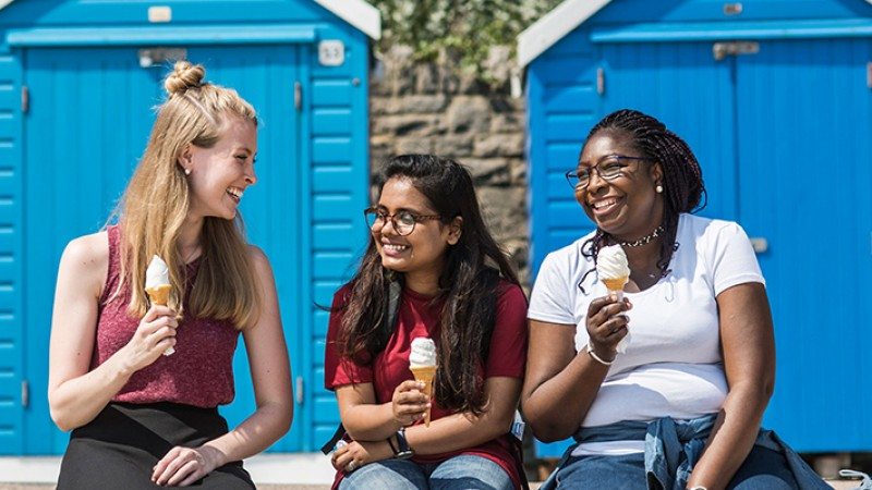 Students with ice cream in front of beach huts