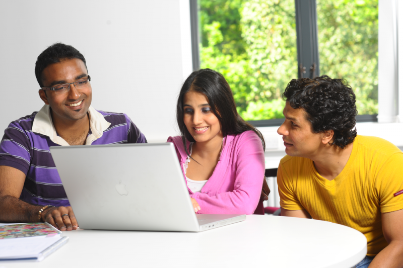 Three students laughing, using a computer