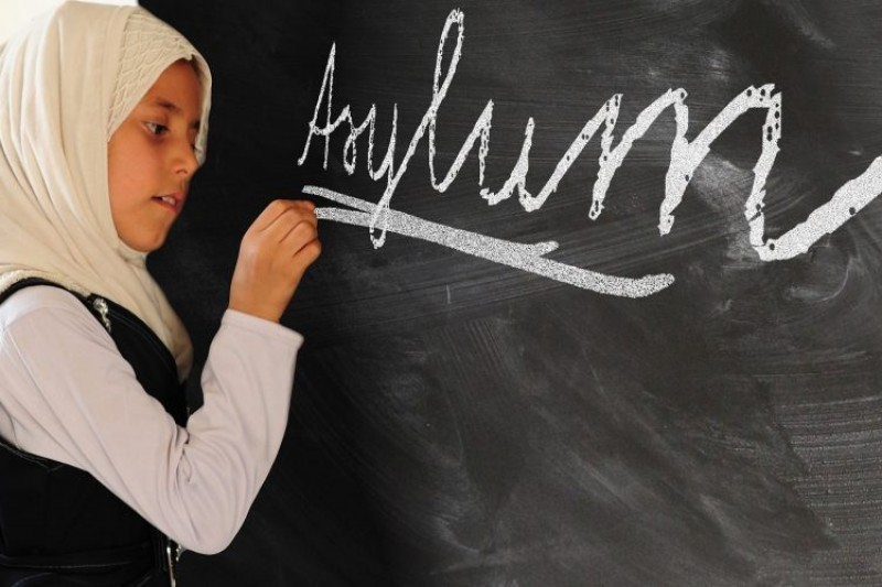 A child writing asylum on a blackboard
