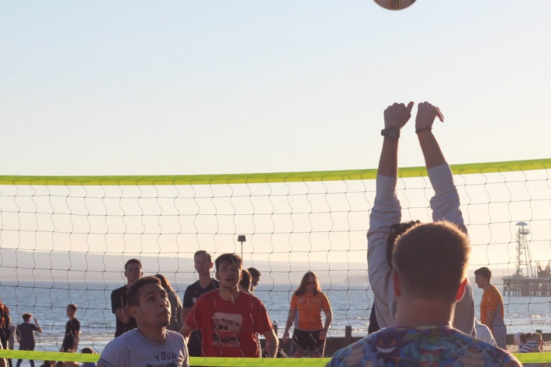 An image of people playing volleyball at a beach BBQ