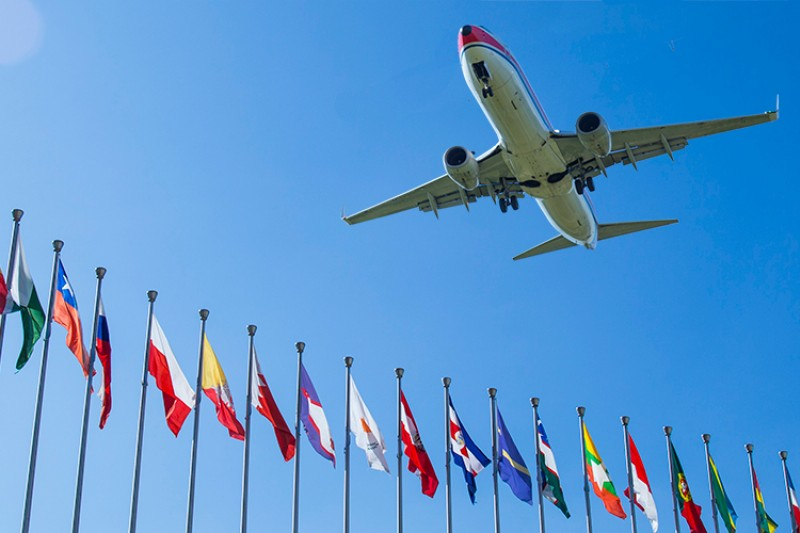 A plane flying over a range of international flags
