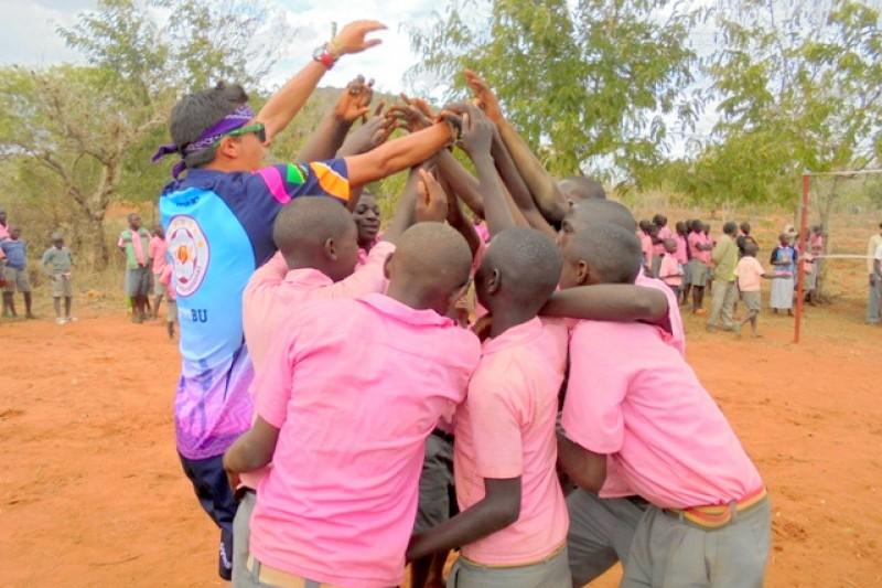 BU student high-fiving Kenyan students
