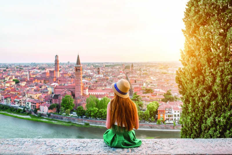 Female in a green dress over-looking a European city