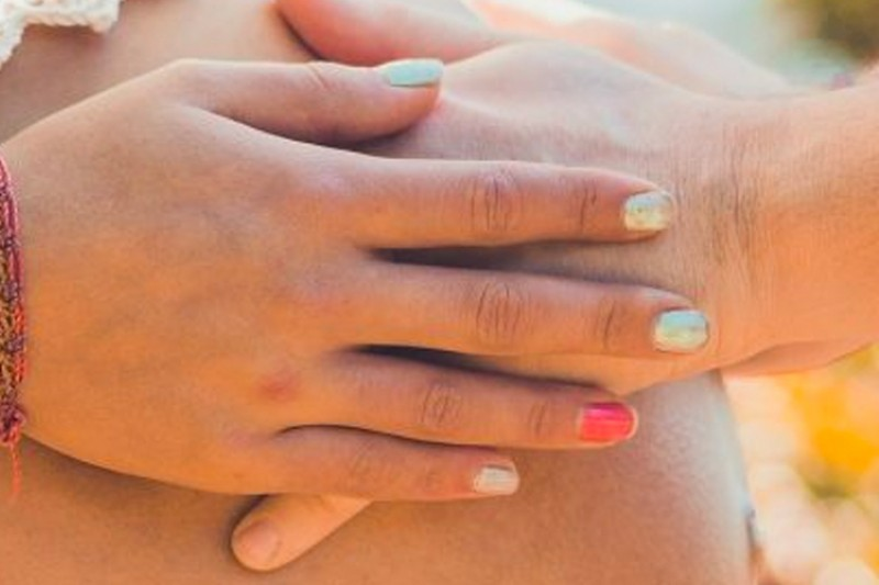 Hands on a pregnant woman's bump