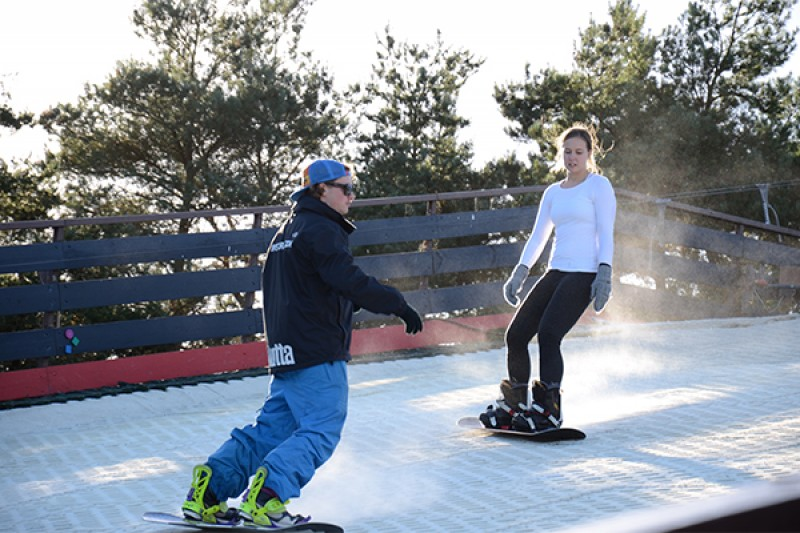Image of two people snowboarding