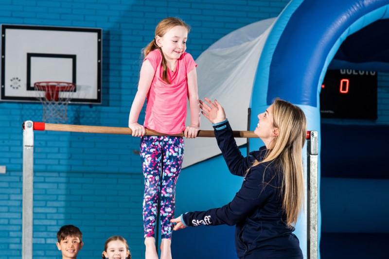 Child and instructor on a gymnastics bar