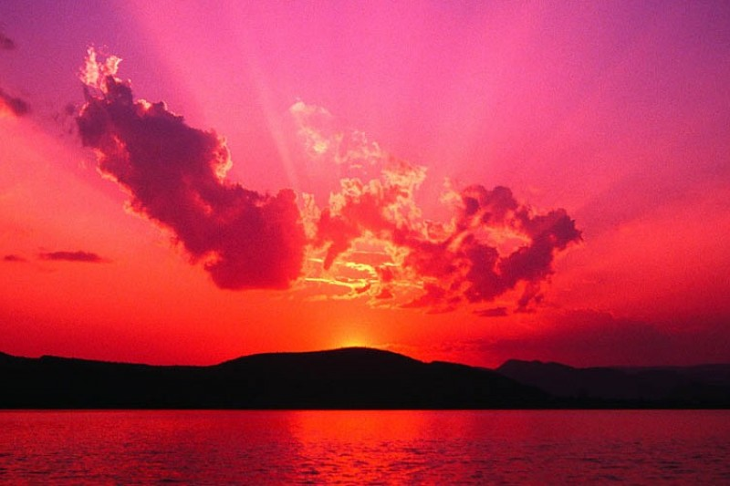 A red sunset over a hilly horizon