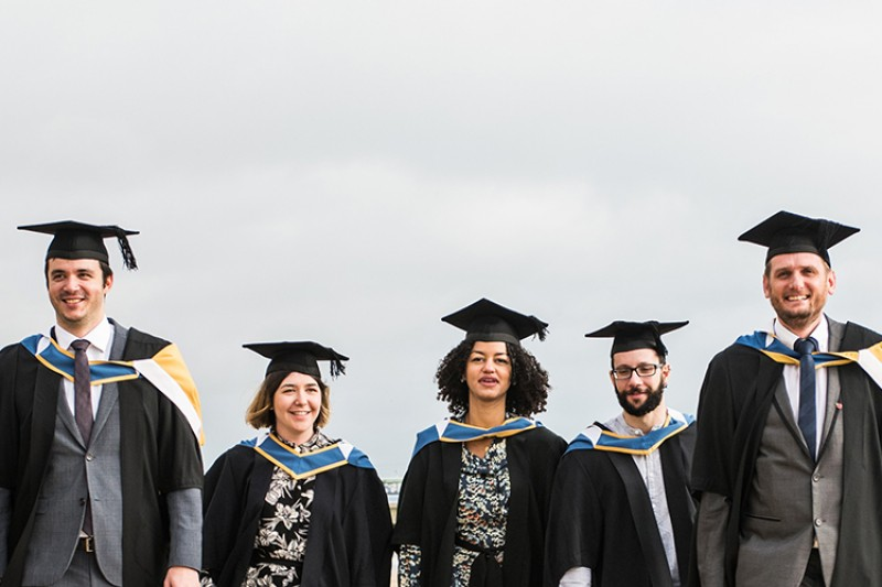 Graduates walking on the beach