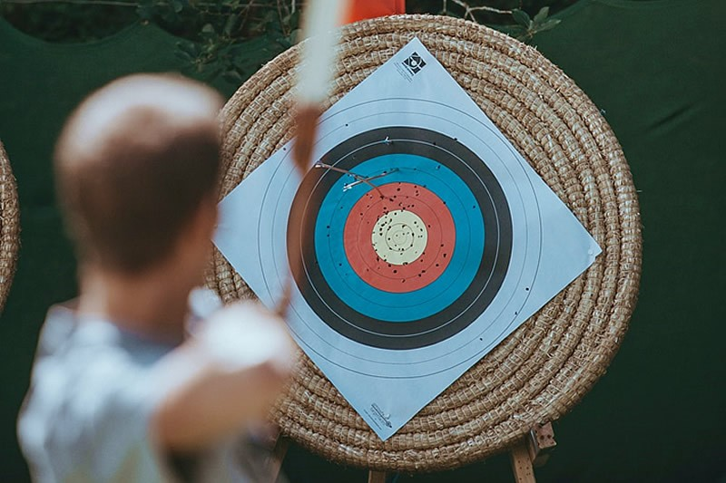 Image of a student holding a bow facing a playing archery target