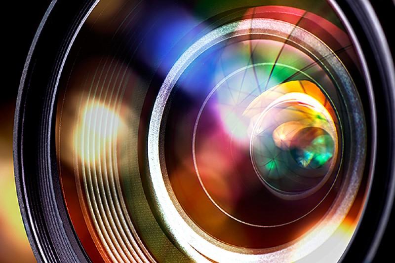 Image of a camera lens against blurred lights