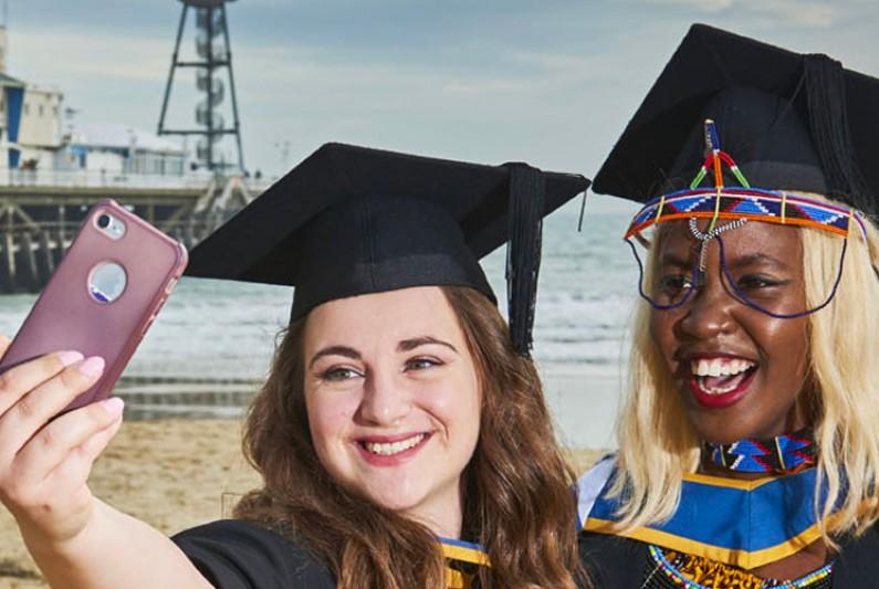 Graduates taking a selfie by the pier