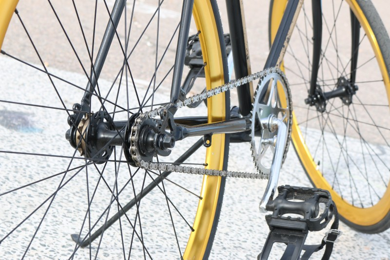 Close up of the pedals, gears and wheels of a black and yellow bike