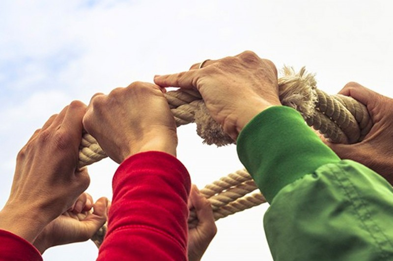 Hands holding a rope in a teamwork exercise