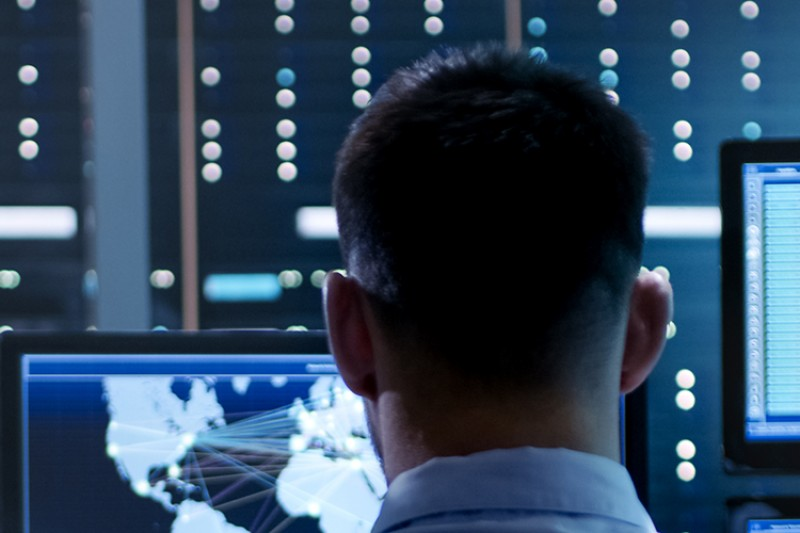 A data analyst surrounded by screens