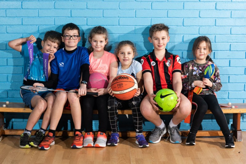 Children sat together on a bench with different balls and racquets used in different sports