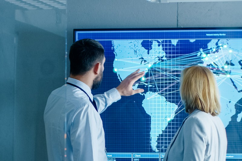 A man and a woman observing a map with data touchpoints