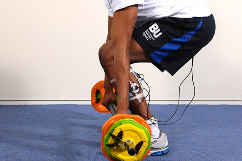 Image of a man lifting bar and weights