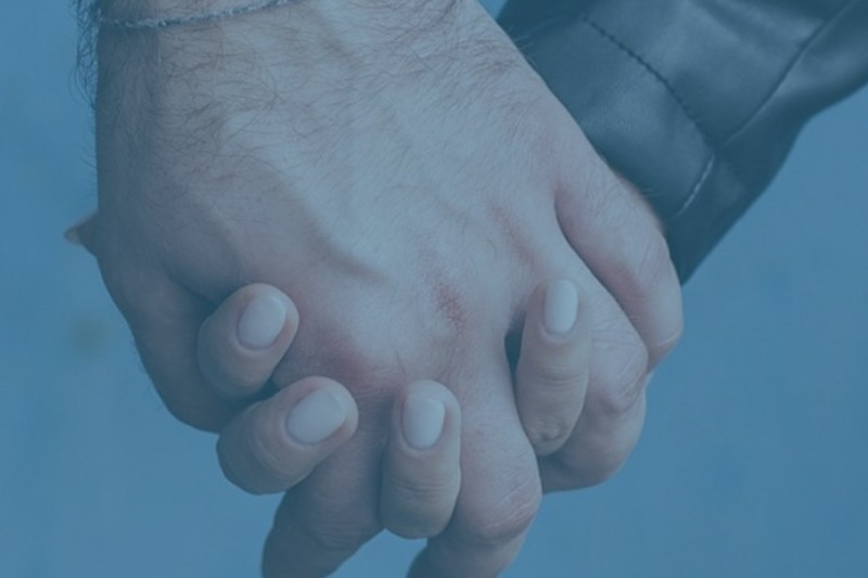 A close up of a man and woman holding hands