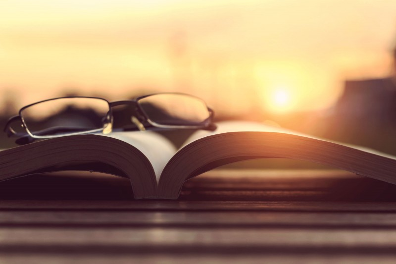 Book and glasses at sunset