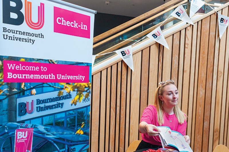 Jess, a student ambassador, showing an Open Day guide book to a visitor