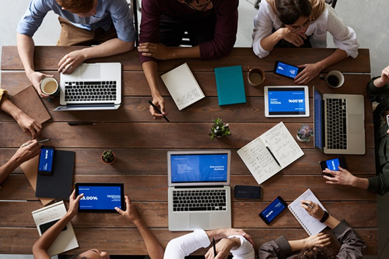 group of people working at table on laptops