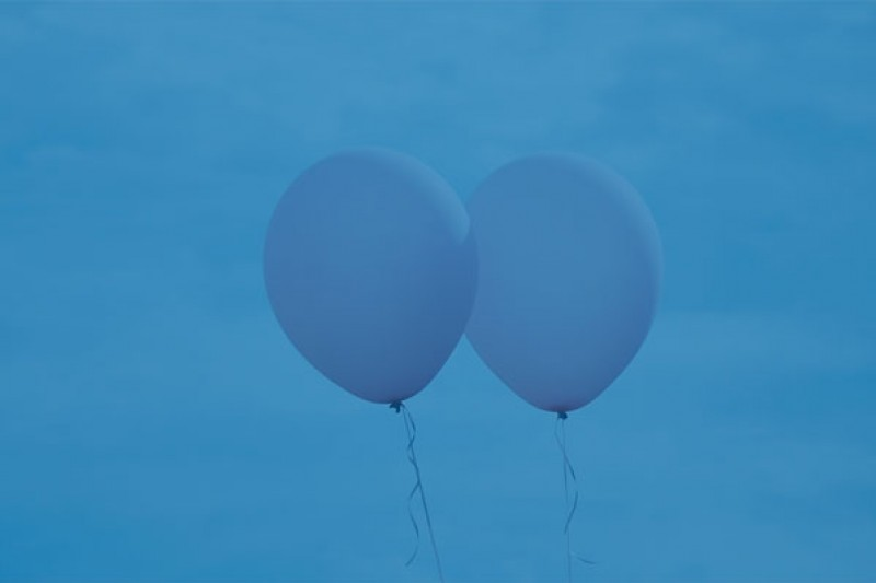 Two balloons behind a blue background