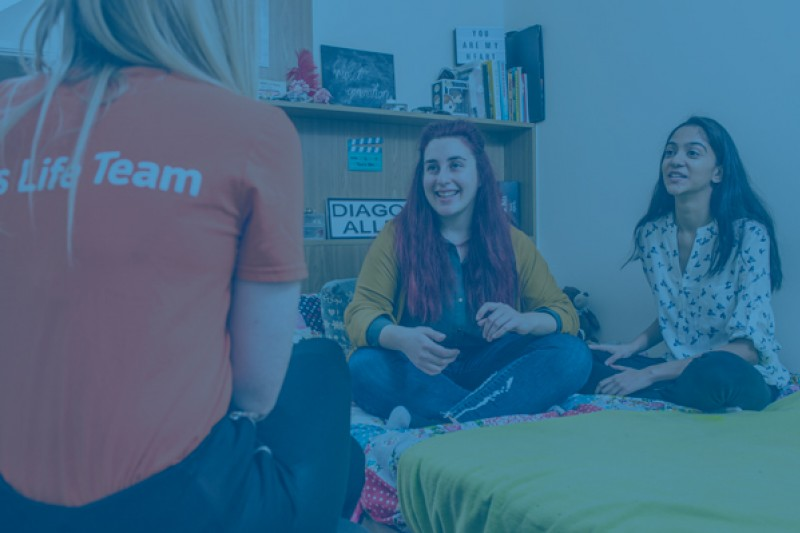Three students talking in a halls of residence room