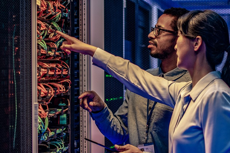 A man and a woman working in a server room