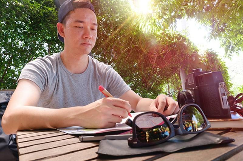 student writing outside