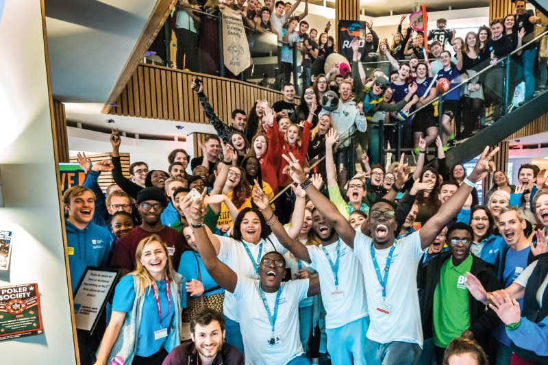 A large group of students and staff in the Student Centre