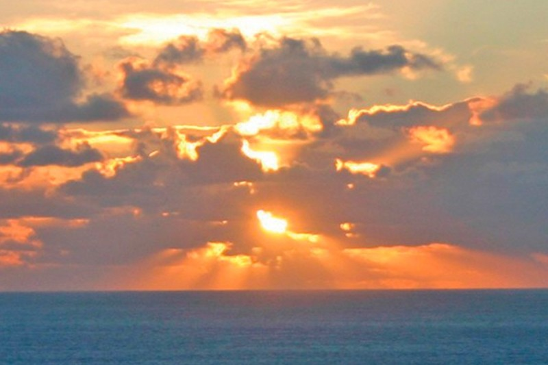Sun breaking through clouds over the sea