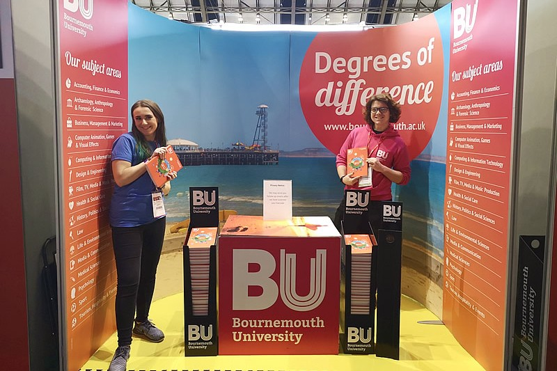 Student ambassadors standing in a BU roadshow stand