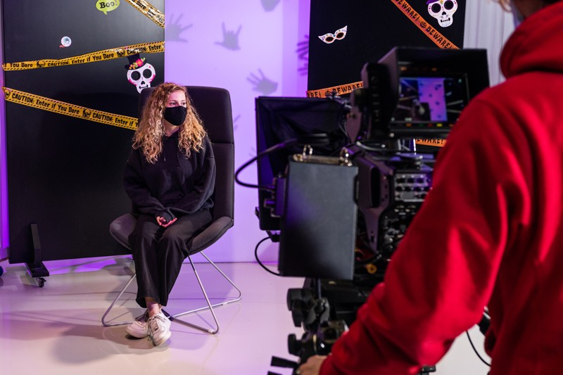 Two students, one manning a camera and one being filmed on a Halloween-themed set, working in a TV studio in Poole Gateway Building