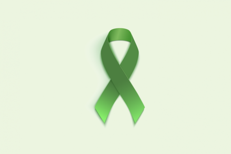 A green ribbon on a green background, representing World Mental Health Day