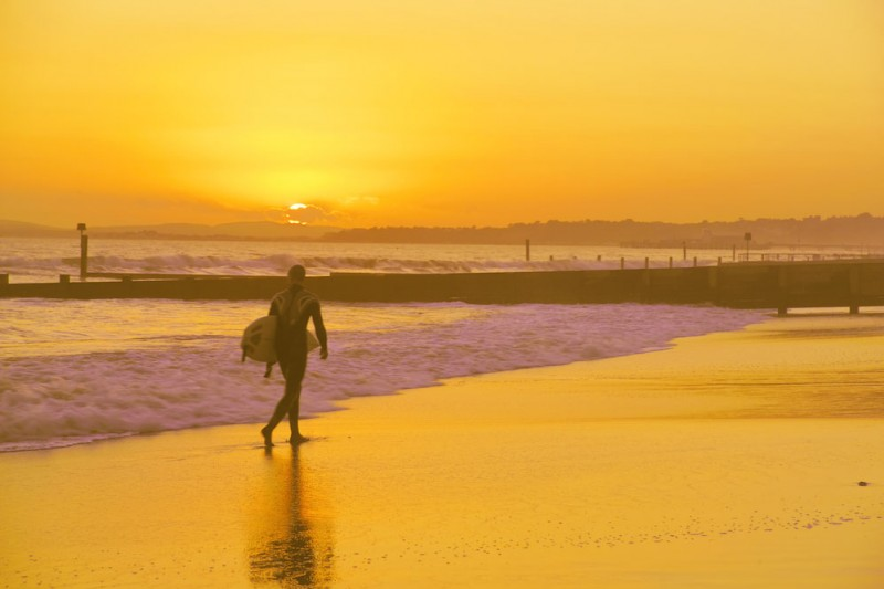 A surfer on Bournemouth beach