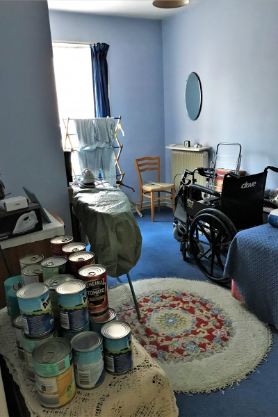 Bedroom with washing rack and tins of food