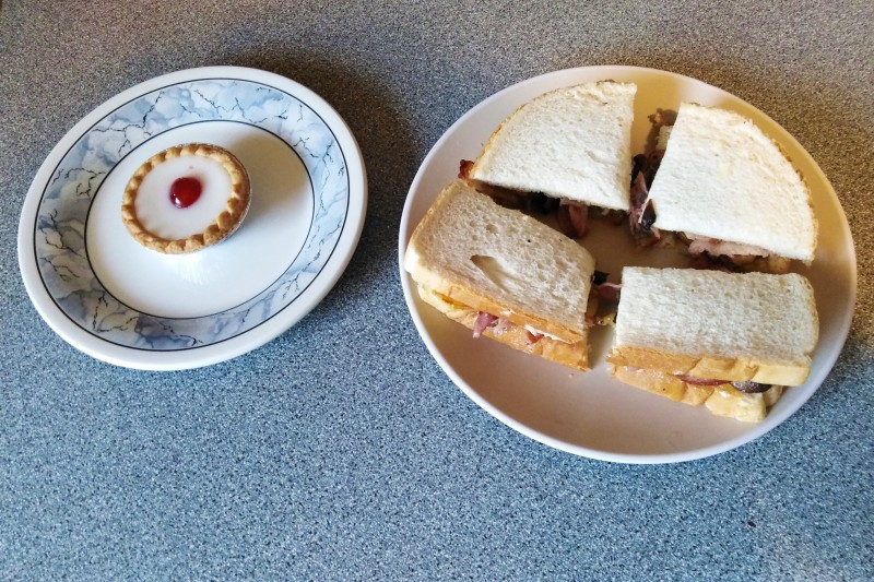 Bakewell tart and bacon sandwich on plates
