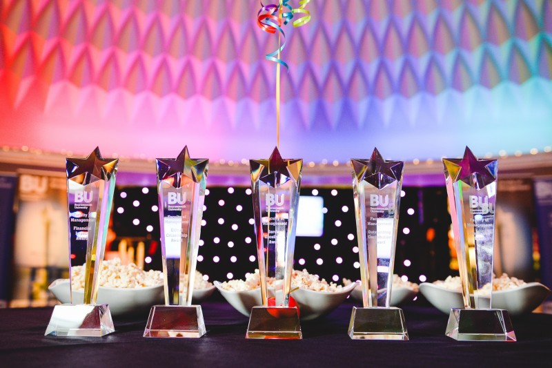 Five award trophies on a table