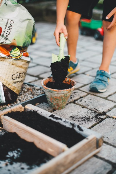 A person using a trowel to move compost