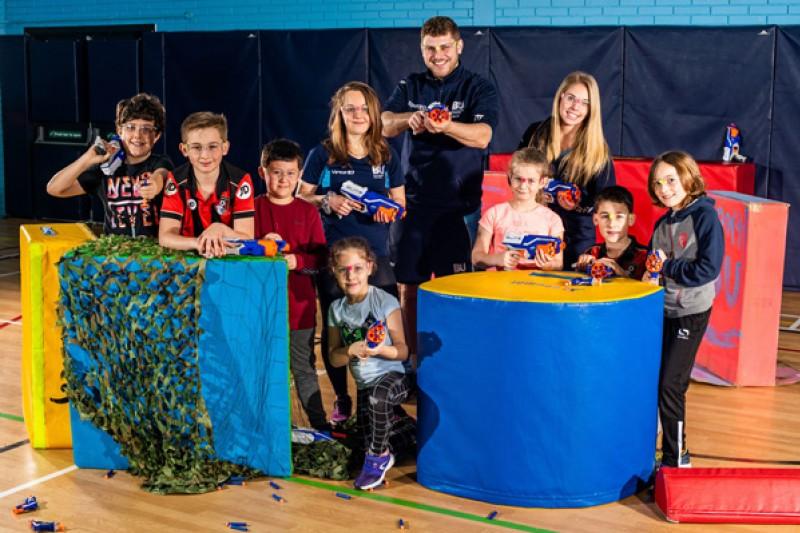 Children at a Nerf war party with SportBU staff