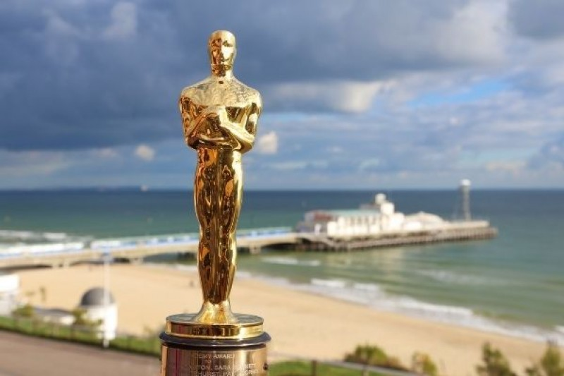 An Oscar statue, with Bournemouth beach and pier in the background